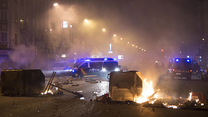 Garbage containers burn near Spanish National Police cars after demonstrators protested against construction plans of turning the main avenue Vitoria into a boulevard, in Burgos